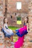 Forme la foto de dos muchachas hermosas en un fondo del ladrillo ru Imagen de archivo libre de regalías