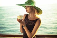 Forme la foto de la mujer elegante que sostiene una taza de café Imagen de archivo