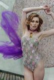 Forme la foto de la mujer joven hermosa en swimgerie de lujo del diseño y encubrimiento púrpura imagenes de archivo