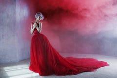 Forme la foto de la mujer magnífica joven en alineada roja Fondo texturizado, humo imagen de archivo