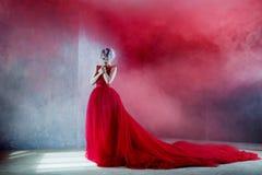 Forme la foto de la mujer magnífica joven en alineada roja Fondo texturizado, humo imagen de archivo libre de regalías