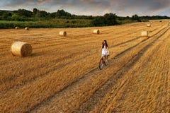 Forme la foto, mujer hermosa que completa un ciclo en un campo de trigo, muchas balas de trigo Fotos de archivo libres de regalías