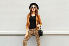 Forme la mirada, la mujer bonita que lleva un sombrero elegante retro, las gafas de sol, la chaqueta marrón y el bolso negro sobr Imagenes de archivo