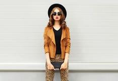 Forme la mirada, la mujer bonita que lleva un sombrero elegante retro, las gafas de sol, la chaqueta marrón y el embrague negro d foto de archivo libre de regalías