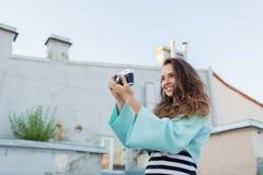 Forme la mirada, modelo bastante fresco de la mujer joven con la cámara retra de la película pelo rizado al aire libre El fotógra Fotografía de archivo libre de regalías