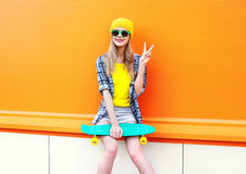 Forme a la muchacha bastante fresca con el monopatín en ciudad sobre naranja colorida Imágenes de archivo libres de regalías
