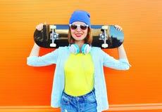 Forme a la muchacha bastante fresca con el monopatín en ciudad sobre naranja colorida Fotos de archivo