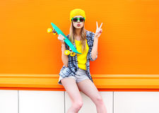 Forme a la muchacha bastante fresca con el monopatín sobre colorido anaranjado Imagen de archivo libre de regalías