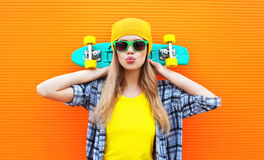 Forme a la muchacha bastante fresca con el monopatín sobre naranja colorida Fotos de archivo