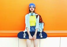 Forme a la muchacha bastante fresca con el monopatín sobre naranja colorida Imagen de archivo libre de regalías