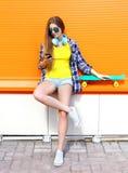 Forme a la muchacha bastante fresca con los auriculares y el monopatín usando smartphone en ciudad sobre naranja colorida Imágenes de archivo libres de regalías