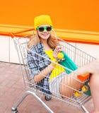 Forme a la muchacha bastante fresca en carro de la carretilla con el monopatín sobre naranja colorida Imagen de archivo libre de regalías