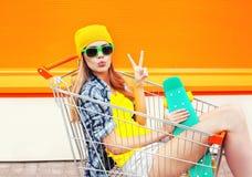 Forme a la muchacha bastante fresca en carro de la carretilla de las compras con el monopatín sobre naranja colorida Imágenes de archivo libres de regalías