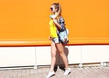 Forme a la muchacha bastante fresca en gafas de sol con la mochila que camina en ciudad Imagen de archivo