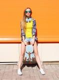 Forme a la muchacha bastante fresca en gafas de sol con la mochila y los auriculares sobre naranja Imagen de archivo