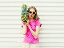 Forme a la muchacha bastante fresca en gafas de sol con la piña sobre blanco Imagen de archivo libre de regalías