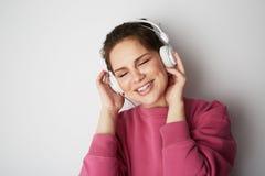 Forme a la muchacha bastante fresca en los auriculares blancos que escucha la música que lleva sudadera con capucha rosada colori Imagen de archivo libre de regalías