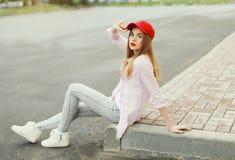 Forme a la muchacha bastante fresca que lleva una camisa y un casquillo rojo Imágenes de archivo libres de regalías