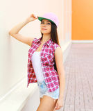 Forme a la muchacha bastante fresca que lleva una camisa y una gorra de béisbol rosadas a cuadros Foto de archivo libre de regalías