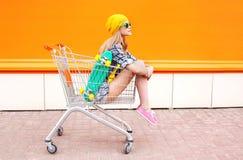 Forme a la muchacha bastante fresca que se sienta en carro de la carretilla sobre naranja colorida Imágenes de archivo libres de regalías
