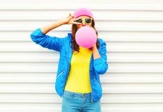 Forme a la muchacha bastante fresca que sopla el balón de aire rosado en la ropa colorida que se divierte sobre el fondo blanco q Imagen de archivo libre de regalías