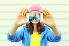 Forme a la muchacha bastante fresca que toma el autorretrato de la foto en smartphone sobre blanco Imagen de archivo libre de regalías