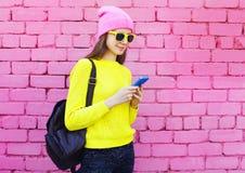 Forme a la muchacha bastante fresca que usa smartphone sobre rosa colorido Fotos de archivo libres de regalías