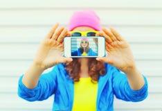 Forme a la muchacha bastante fresca tomando a autorretrato de la foto en smartphone sobre llevar blanco del fondo la ropa y las g Imagen de archivo libre de regalías