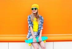 Forme a la muchacha bastante rubia con el monopatín en ciudad sobre naranja colorida Foto de archivo libre de regalías
