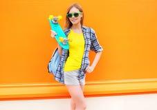 Forme a la muchacha bastante sonriente con el monopatín sobre naranja colorida Foto de archivo