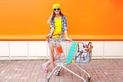 Forme a la muchacha bonita con el carro y el monopatín de la carretilla de las compras sobre naranja colorida Imagen de archivo