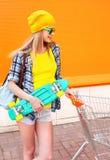 Forme a la muchacha bonita con el monopatín del carro de la carretilla de las compras sobre naranja colorida Imagen de archivo