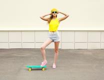 Forme a la muchacha bonita con el monopatín en ciudad sobre blanco Fotos de archivo libres de regalías