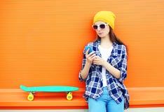 Forme a la muchacha bonita con el monopatín usando smartphone sobre colorido Imagen de archivo
