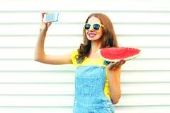 Forme a la muchacha bonita con una sandía que toma el selfie de la imagen en el smartphone sobre el fondo blanco Foto de archivo libre de regalías