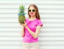 Forme a la muchacha bonita en gafas de sol con la piña sobre blanco Imagen de archivo libre de regalías