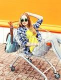 Forme a la muchacha bonita llevando las gafas de sol que se sientan en carro de la carretilla de las compras Fotos de archivo