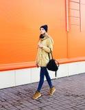 Forme a la muchacha bonita que camina en la ciudad sobre naranja Fotografía de archivo libre de regalías