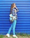 Forme a la muchacha bonita que lleva una camisa de tela escocesa con la mochila sobre azul Imagen de archivo
