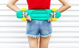 Forme a la muchacha con el monopatín en pantalones cortos del dril de algodón sobre el fondo blanco Fotografía de archivo libre de regalías