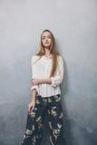 Forme a la muchacha del adolescente que se opone a fondo texturizado azul de la pared del grunge Imagen de archivo libre de regalías