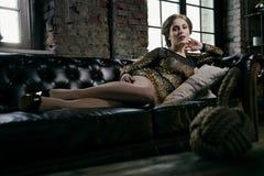 Forme a la muchacha del encanto que miente en un sofá de cuero negro Fotos de archivo libres de regalías