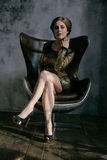 Forme a la muchacha del encanto que se sienta en silla de cuero marrón Foto de archivo libre de regalías