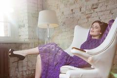 Forme a la muchacha del encanto que se sienta soñador en la silla blanca Fotografía de archivo