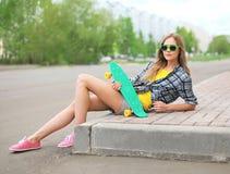Forme a la muchacha del inconformista en gafas de sol con la presentación del monopatín Imagen de archivo libre de regalías