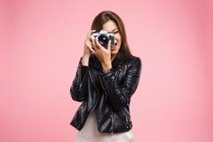Forme a la muchacha en la chaqueta de cuero negra que sostiene la cámara vieja Fotografía de archivo
