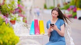 Forme a la muchacha feliz con los bolsos después de café de consumición que hace compras en café al aire libre Venta, consumerism almacen de video
