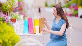Forme a la muchacha feliz con los bolsos después de café de consumición que hace compras en café al aire libre Venta, consumerism almacen de metraje de vídeo