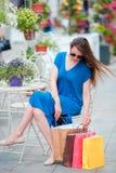 Forme a la muchacha feliz con los bolsos después de café de consumición que hace compras en café al aire libre Venta, consumerism Fotografía de archivo libre de regalías