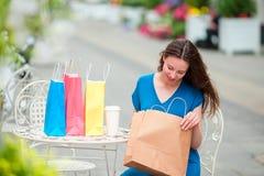 Forme a la muchacha feliz con los bolsos después de café de consumición que hace compras en café al aire libre Venta, consumerism Imágenes de archivo libres de regalías